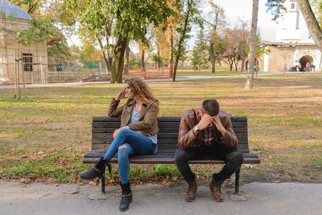 couple in a fight sitting on a park bench
