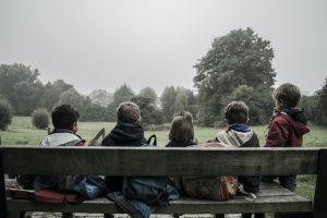 Children socializing on bench outside.