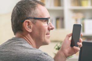 Man with hearing aid checks his phone.