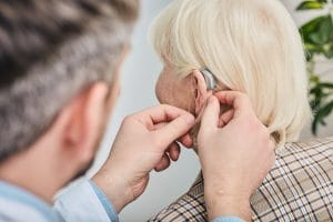 Audiologist inserting hearing aid on a woman's ear